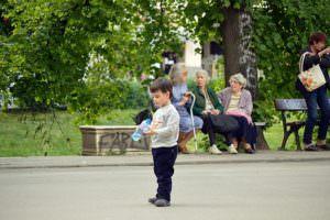 boy holding bottle in front of older women sitting on park bench