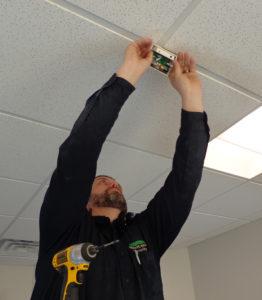 Technician Adam begins to install a glass break sensor