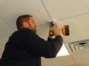 Technician Adam screws a glass break sensor onto a drop ceiling
